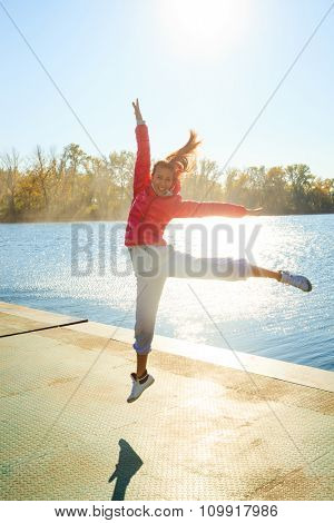 happy young woman jumping on pontoon at lake in red winter jacket and tracksuit, sunny autumn day, full body shot