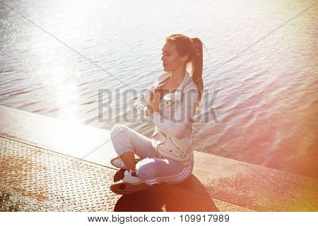 young woman in tracksuit practice yoga outdoor by the lake, sunny autumn day, full body shot