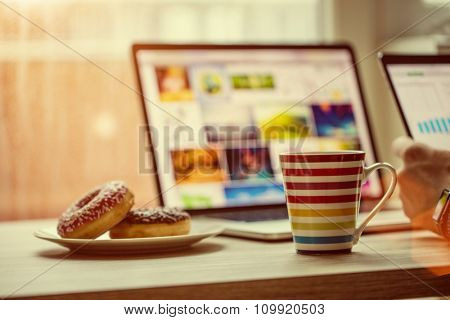 Man working on notebook, with a fresh cup of coffee.