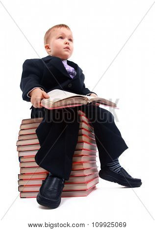 Portrait of asian schoolboy holding a book and sitting on a stack of books isolated on white