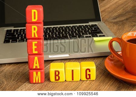 Dream Big written on a wooden cube in a office desk