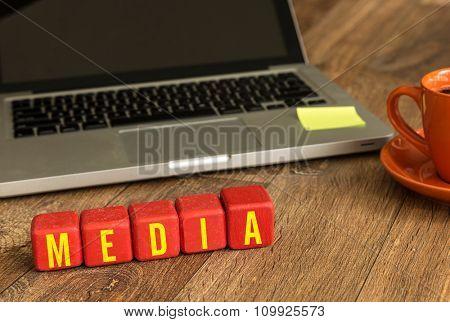 Media written on a wooden cube in a office desk