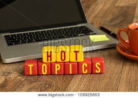 Hot Topics written on a wooden cube in a office desk