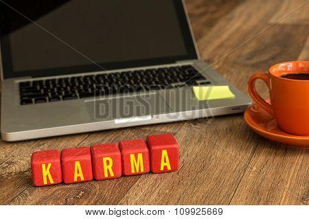 Karma written on a wooden cube in a office desk