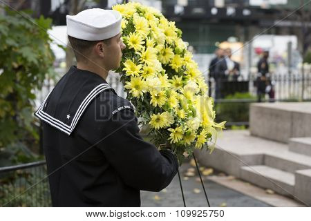 NEW YORK - NOVEMBER 11 2015: A sailor from the USS New York carries a wreath of flowers to the Eternal Light Monument for ceremony in Madison Square Park before the Americas Parade on Veterans Day.
