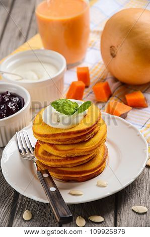 Pumpkin pancakes on white plate with pumpkin smoothie and cream fresh