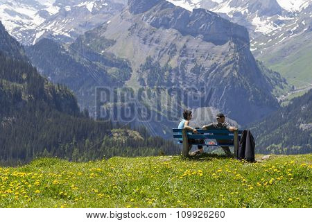Kandersteg, Switzerland - 7 June 2014: Couple Sitting On Bench Observing Amazing View Of Swiss Alps
