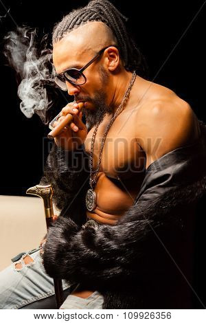 Muscular Man with Cigar and Sunglasses on Black Background