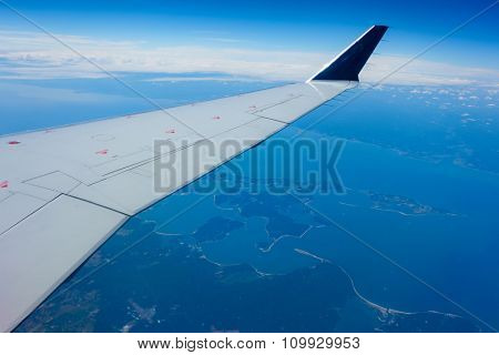 Wing of an airplane flying above a coastal region.