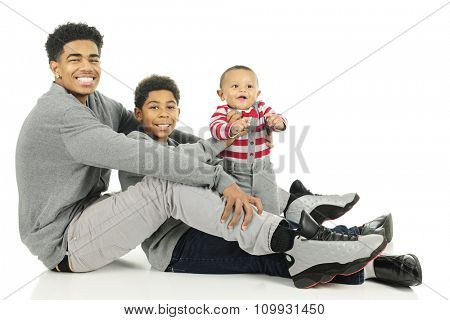 Three widely-spaced brothers sitting train-style from the tall teen oldest to the infant youngest.  On a white background.