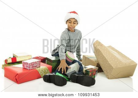 An elementary boy sitting on the floor while happily looking over his stash of unopened Christmas gifts.  On a white background.
