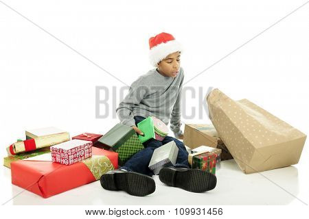 An elementary boy who has fallen while carrying a many Christmas gifts.  He's now on the floor with wrapped gifts all around.  On a white background.