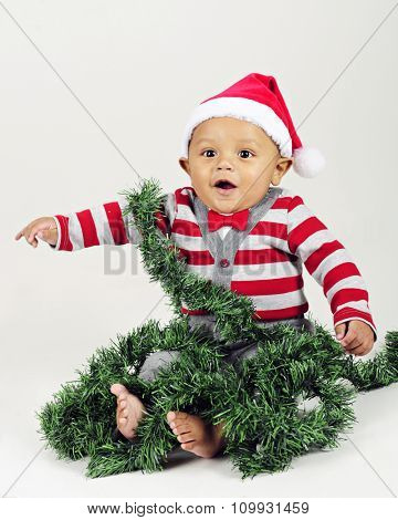 An adorable baby boy wearing a Santa hat and red bow tie delighted with Christmas.  He's sitting wrapped in Christmas garland.  Isolated on gray.