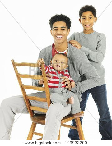A portrait of three widely-spaced brothers -- the oldest sitting on a chair backwards while holding his baby brother, his elementary brother standing behind.  On a white background.