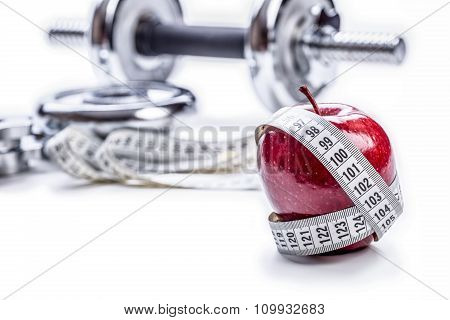 Fresh red apple, tape measure, and in the background Fitness dumbbells. Healthy lifestyle diet