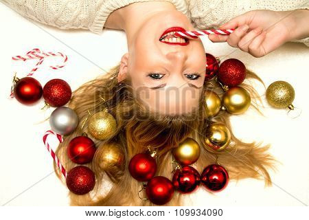 Beautiful Blonde With A Christmas Candy Lying On A White Background.