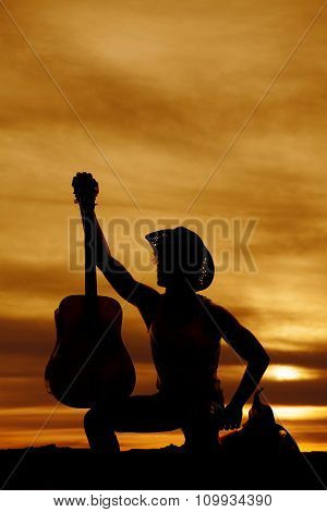 Silhouette Of A Cowboy Sitting On A Saddle Holding A Guitar