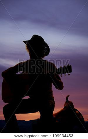 Silhouette Of A Cowboy Sitting On A Saddle Playing A Guitar