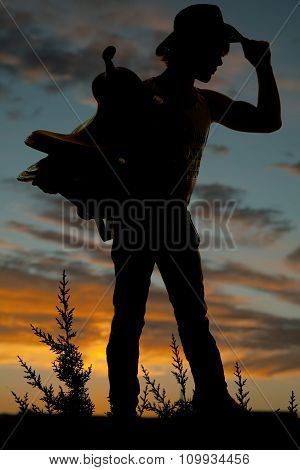 Silhouette Of A Man Holding A Saddle And Touching His Hat