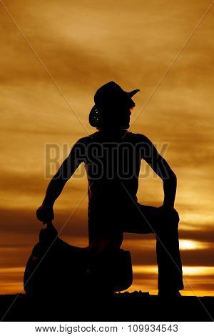 Silhouette Of Cowboy Kneeling By Saddle Look To Side