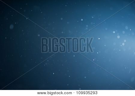 winter night scene, falling snow background snowflakes in blur over dark background