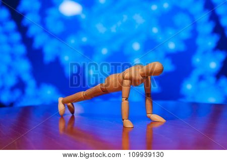 Wooden dummy, mannequin or man figurine exercising - doing a plank, press-up, push-up on blue backgr