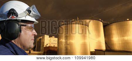oil and gas industry, worker in close-ups with giant fuel-storage tanks, sunset time