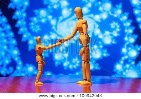 Two wooden dummy, mannequin or man figurine shake hands on blue background. Handshake