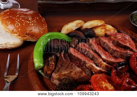 fresh roast bbq beef meat ribeye steak on wooden plate served with tomato juice iwooden cup, boiled broccoli, baked tomatoes and potatoes, with white bun, red wine glass light walnut wooden table
