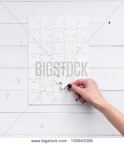hand holding a piece of white uncompleted puzzle on white wooden background