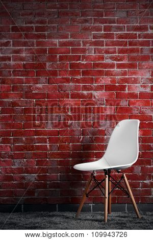 White modern chair on brick wall background