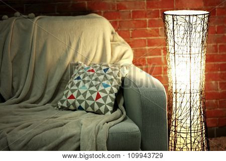 Comfortable sofa and modern lamp on brick wall background