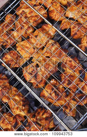 fresh raw chickn in meat holder on grid grill over burned charcoal spiced with salt pepper paprika ready to serv party