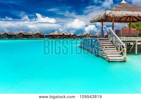 Small boat jetty on a tropical island of Maldives with vibrant blue lagoon