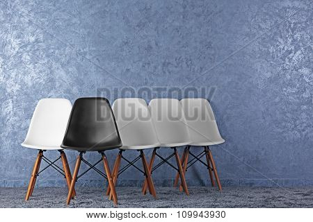 Stylish conception with white and black chairs on grey background