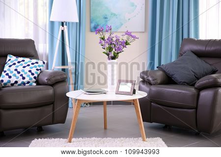 Modern living room interior with coffee table, armchairs and stand