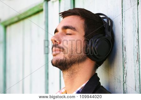Young man listening to music on a house wall background