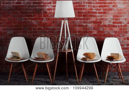White modern chairs with lamp and books on brick wall background