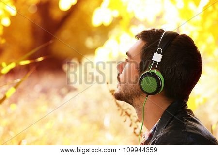 Young man sitting under the tree and listening to music