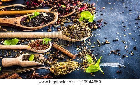 Various kinds of tea in wooden spoons on black table