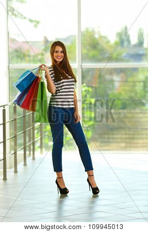 Young pretty woman with shopping packages  in the shop