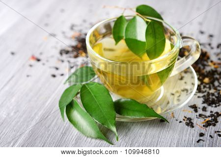 Glass cup of tea with green leaves and scattered tea around on grey wooden background