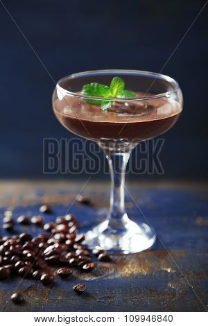 Chocolate dessert in glass on color wooden background