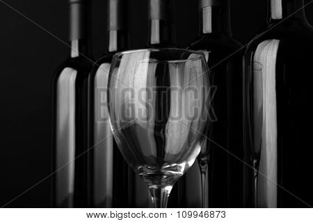 Glass and wine bottles in a row on black  background, close up