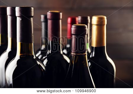 Wine bottles on wooden background, close up