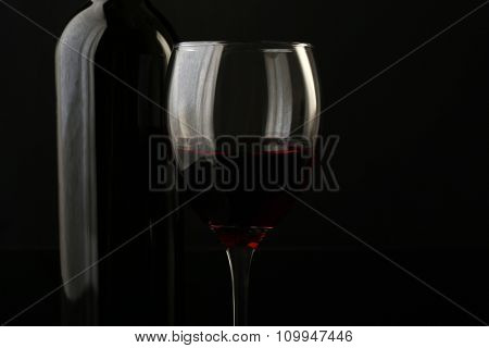 Red wine glass and bottle on black background, close up