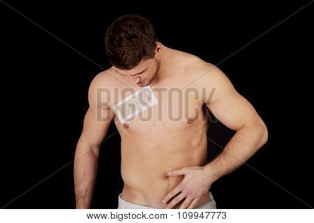 Handsome muscular man waxing his chest.