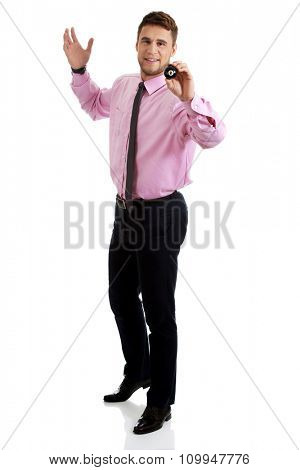 Young handsome businessman holding billiard ball.