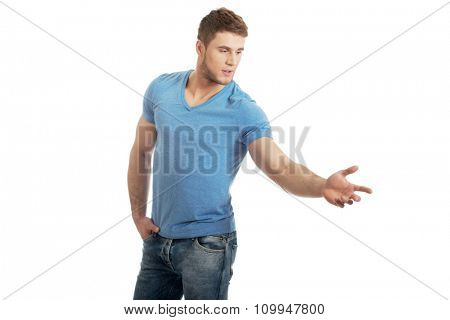 Handsome young casual man pointing down.