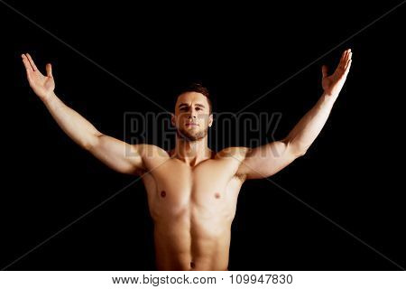 Handsome muscular man with his hands up.